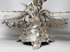 This superb figural serving piece makes a stunning show. An antique silver plated table epergne with a centre flower vase and 2 serving dishes. The central support is in the form of a young girl and a cherub on a naturalistic base with flowers, foliage and tall grasses. The pretty cut crystal flower vase is removable. Length 50 cms. Height 34 cms, 44.5 cms to top of the glass vase. The side dishes measure 18 x 22 cms. Stamped under one foot WMF. Made in Germany. Circa 1880.