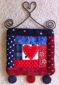 Mini quilt art wall hanging in red white and blue with a red heart