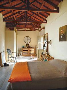 Στην ταράτσα, εκεί όπου κάποτε ήταν τα πλυσταριά, δημιούργησε το λιτό και κομψό υπνοδωμάτιό του με την ιδιαίτερη ξύλινη στέγη