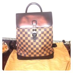 Louis Vuitton Damier Soho Backpack This stylish backpack is the signature Damier check on toile canvas. It features a chocolate cowhide leather base and lengthy adjustable shoulder straps with brass hardware and s top flap with a rolled leather top handle. This opens to a spacious red fabric interior with pockets. In excellent used condition. Authentic! Louis Vuitton Bags Backpacks