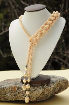 This bead crochet rope must be tremendously long to be knotted that much an still have as much length as it does,