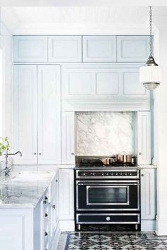 A pale blue kitchen with marble backsplash and tiled floors
