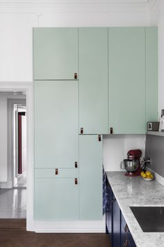 mint green cabinets with leather pulls. I die.