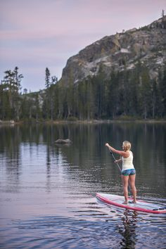 A young woman enjoying an evning paddle board seesion on a mountain lake in Northern California.