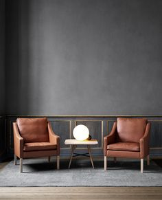 A pair of 2207 Lounge Chairs by Børge Mogensen. Mogensen designed the 2207 in 1963 as part of a series including a 2 and 3 seater sofa. Stunning moody decor with tan leather armchairs produced by Danish brand Fredericia.