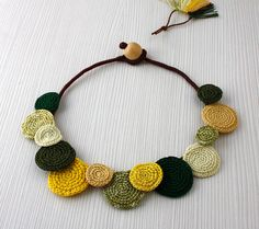 Art-looking statement necklace!  The basic string is hand made by me from a cotton thread wrapped around a cord, the necklace is buttoning with a