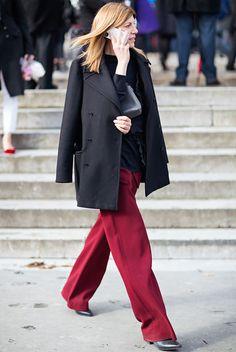 Street style que quebra o look todo preto com uma calça vermelha.