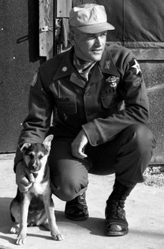 """Maj. Roger Donlon, the first Medal of Honor recipient of the Vietnam war, poses outside his headquarters tent at the Advanced Combat Training Academy. With him is the camp's mascot, """"Lieutenant."""" Donlon was serving as commander of the academy, which trained NCOs and small-unit leaders in scouting and patrolling techniques. """"We work all our students pretty hard,"""" he said, """"but nobody ever died from overwork. You can die from not being worked hard enough."""" © Stars and Stripes"""