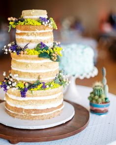 """Only one of the two cakes served at this wedding, the large """"naked"""" style blueberry-lemon cake by Buttercup Bakery boasted bright crowns of fresh flowers."""