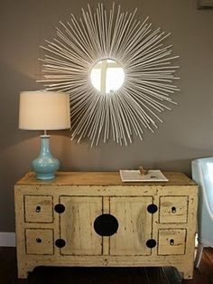 Buy a cheap round mirror and hot glue dowel rods to back of mirror (spray paint rods any color you want). Love this!! What a great idea!