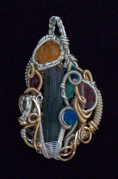 Pendant | Daniel of Twistedwerx. Tourmaline, spessartite garnet, herkimere diamond, blue apatite, yelllow diopside, scapolite, spinel and emerald.  hand sculpted with sterling silver and 14/20 gold filled.