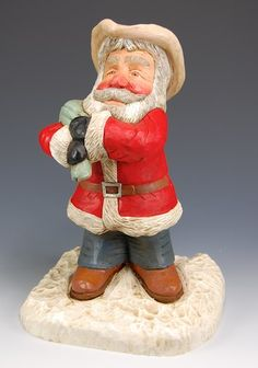 Cowboy Santa Claus-carving on snowy wooden base, all carved from one piece of wood. This western Santa wears a traditional red Santa coat, black mittens, cowboy boots, blue jeans, a well loved cowboy hat and has a toybag full of goodies thrown over his shoulder. A very special and unique, one of a kind wooden Santa.