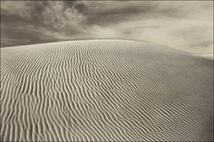 Sand dune at White Sands National Monument, New Mexico. Black and White photograph. Image title: Patterns in the Sand This image is from my photography series of Southwest landscapes. The sand dunes at White Sands National Monument is an interesting place. The many shifting patterns in the sand vary with location and shape of the dunes. In the sand, you can see the tracks of small animals as they traverse from place to place. All photographs are original and photographed by artist Bob...