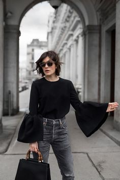 Black ruffled sleeves and gray jeans