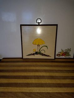 This is a cute little Yellow Mushroom wooden wall plaque It is hand painted and signed Patsy 74 It has a round brass ring attached to hang it by. There is a little bit of damage, a place on the bottom, on the side and a scratch on the front. All are pictured. It measures 8 x 8 x 1