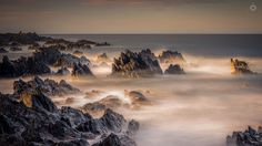 Mountains in the Cloud - A long exposure, landscape image of rocks getting battered by waves in the evening sunshine at Sandend in Aberdeenshire, Scotland.