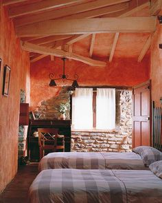 A faux plaster wall finish, coupled with the elements of exposed brick and rough wood beams for additional texture, turns this attic bedroom into a private hideaway with Tuscany appeal.  The corner cross beam especially softens the corner and is appealing to the eye.