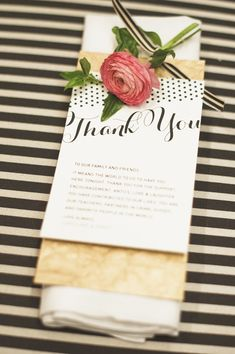 wedding place setting with pink ranunculus, black and white stripe