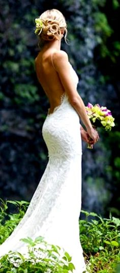 Beach bride's looped bun hairstyle with orchid gorgeous low backless wedding gown