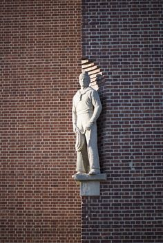 #Kiel Zweiechte Kerle – ein Matrose und ein Werftarbeiter – stehen stolz und kräftig wie WachfigurenamEingangsbereich des Ende der 1930er Jahre als Verwaltungsbau des Marinearsenals gebauten Gebäudes....