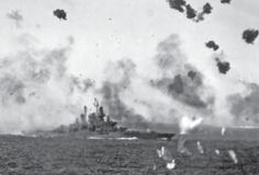 Flak still clouds the sky above the USS Tennessee following a successful strike by an Aichi D3A Kamikaze on April 12th, 1945. The attack was part of a mass wave, a strategy instituted by the Japanese that month as the Allies encircled Okinawa. Known as Operation Kiksui (Floating Chrysanthemum), hundreds of planes were sent out at one time in the hopes of simply overwhelming Allied air defense to ensure some number would reach their target. The attacks, spaced over April and June, expended…