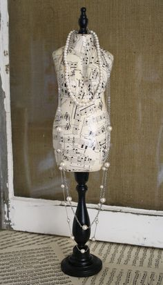 Paper mache mannequin made into jewelry stand created with decoupage and sheet music