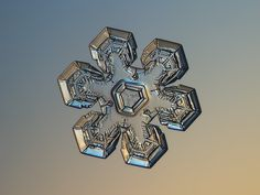 Snowflake image: Massive gold, real snow crystal with relief and glossy surface, sparkling on bright blue-orange gradient background in warm golden light