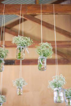 Decorando com vidros e flores pendurados no teto de madeira