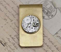 """Steampunk Money Clip  A gorgeous antique brass vintage money clip has been repurposed into this vintage style Steampunk money clip. Perfect gift for all the men in your life. These also make great groomsmen's gifts. All of our  Money clips are vintage and are meant to be rough around the edges and will have scratches and scuffs. 1 7/8 x 1""""   All of our items are packaged and ready to give as gifts.  ..."""
