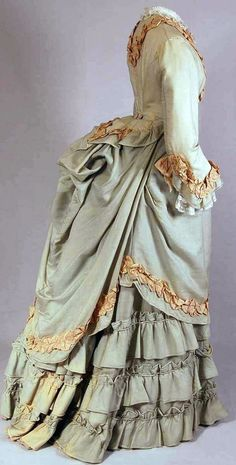 Two-piece day dress, Nice, France, ca. 1870-75. Light green cotton/wool with beige pleated silk trim. Bodice lined with cotton, closes with fabric covered buttons.  Skirt with pleats in back, hem reinforced with cotton and woolen band, closes with hooks and eyes at waist - Mode Museum, Antwerp