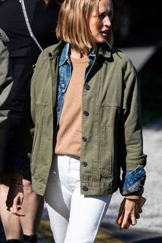 Layered Spring Outfit Idea — Army green jacket, camel sweater, denim jacket, and white jeans.