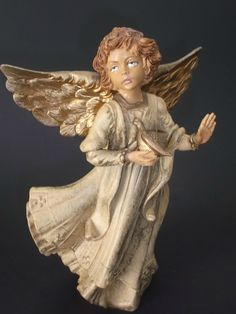 Here is a beautiful vintage angel figurine holding a  dove, made in Italy from a thick heavy resin, plastic material.  She is painted in a tan color  at Saltymaggies Treasures on Ruby Lane