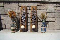 """Bombay Metal Sconce Candle Holders Mounted on Reclaimed Wood  We have a set of Bombay metal sconce candle holders that are attached to two beautiful interesting pieces of reclaimed wood. We cut a bevel in each piece and lightly sanded and added two coats of clear coat to help bring out the natural beauty of the wood. The saw cuts and nail holes stand out adding character to the pieces.  They both measure approx. 22"""" x 5 1/2"""" x 3/4"""""""