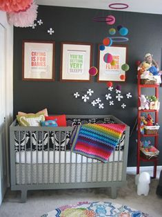 a pop of color, rainbow against a grey wall and black and white crib