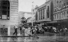 A group of people crossing Edward and Queen Streets, Brisbane, in March 1940. Looking east towards Elizabeth Street. The building on the left is the third Australian Mutual Provident (A.M.P.) Society building, also known as Macarthur's Chambers, erected in 1930-34. A number of cars are driving along Edward Street, including a Bayards department store delivery van. Traffic lights can be seen on the left side of the intersection.