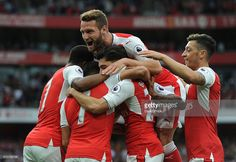 Alexis Sanchez celebrates scoring Arsenal's 1st goal with his team mates and Shkodran Mustafi during the Premier League match between Arsenal and Chelsea at Emirates Stadium on September 24, 2016 in London, England.