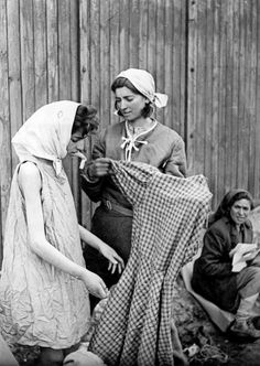 Newly liberated Jewish women at Bergen-Belsen concentration camp are given clean clothing after showering and being deloused. Ita Deutsch (right) helps her frail sister Friedel Deutsch (left) into a new, clean dress.... Although Friedel lived to see the camp liberated, she died in the camp of typhus a few days after this photograph was taken. Bergen-Belsen concentration camp, Near Celle, Lower Saxony, Germany. 18 April 1945.