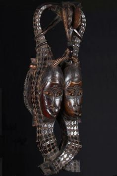 Africa | Mask with Crocodiles.  West Africa | This mask celebrates the harmony between two kindred spirits. This harmony can be inferred from the interlocking of the two heads by the bird and the crocodiles. The bird binds the two tails while wrapping its own limbs around them and holding by its beak a connection between both heads. These represent harmony in thought as well as the likeness of the two faces.