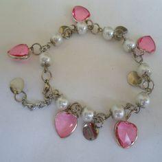 Pulseira feita com peróla tcheco, coração em acrílico rosa com acabamento em abs e pingentes prateado. R$ 4,50