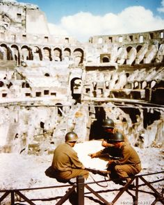 5th Army soldiers study a map of Rome. In background is the ruins of the Coliseum. Italy