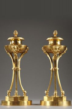 A Pair of gilt bronze tripods candlesticks, composed of a circular base extending by three incurved pilasters decorated with heads of satyrs on which rests a vase à l'antique... 3,700€