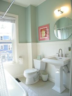 White wainscoting with a wide baseboard, twin sconces and a glass shelf over the pedestal sink in a bathroom. Description from pinterest.com. I searched for this on bing.com/images