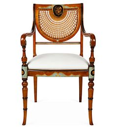 Sheraton-style cane-backed armchair.Thomas Sheraton's pieces represent an interval style carved out between Adam's delicate Neo-Classicism and England's high-glamour Regency Style