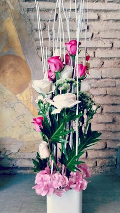 Vertical floral arrangement with pink roses in white ceramic vase