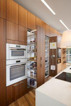 cuisine en longueur, îlot en noir et blanc, des meubles sur toute la longueur du mur, avec des étagères glissantes