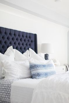 Beautiful blue and white cottage bedroom features white and blue bedding topped with a blue and white sequined lumbar pillow and complementing a dark blue tufted wingback headboard.