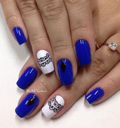 Royal blue and white winter nail art design. Paint on adorable lace details with black polish on the white base and add black diamond embellishments on top for a perfect accent.