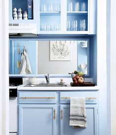 Such a unique redo. And even used existing cabinetry. Blue kitchen cabinets with brass hardware and mirror backsplash