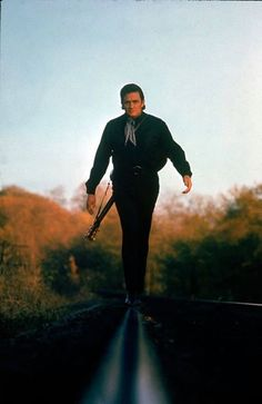 Johnny Cash walking along the line of a railway track with his guitar strapped across his back, 1969. Photograph by Michael Rougie.