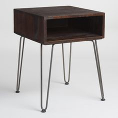 With a simple mid-century-inspired profile, our petite side table features a rustic brown mango wood cubby on black metal hairpin legs. This versatile table is ideal as an end table next to the sofa or as a nightstand in the bedroom.